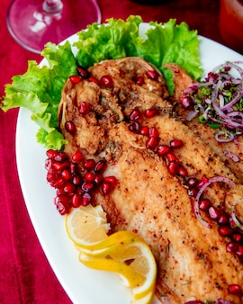 Fried fish served with pomegranate lettuce onion and lemon slices