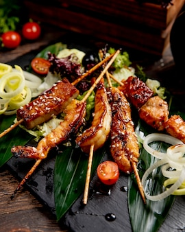 Fried fish and shrimps on sticks served with lettuce tomatoes and onions