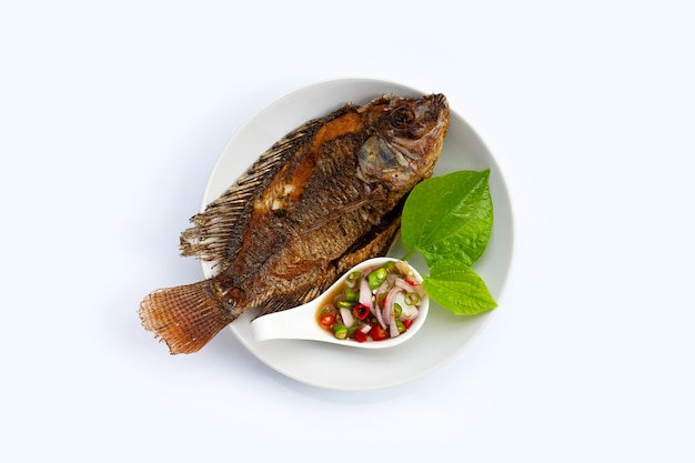 Fried fish in white plate on white background.