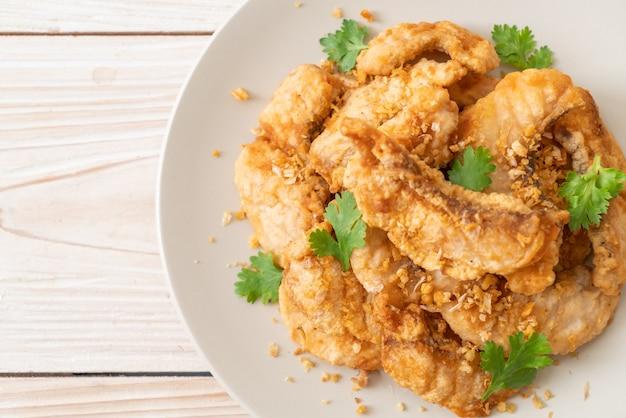 Жареная рыба с чесноком на тарелке