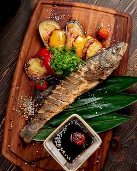 Жареная рыба с жареными баклажанами, болгарским перцем, помидорами и соусом