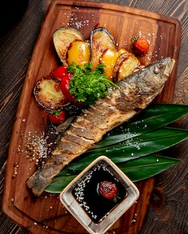 Fried fish with grilled eggplants bell peppers tomatoes and sauce