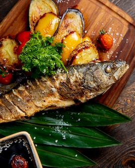 Fried fish with grilled eggplants bell peppers and tomatoes