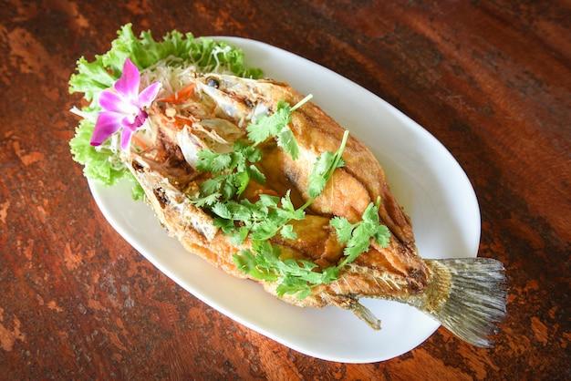 ハーブと野菜の揚げ魚、木製テーブルのプレート上の調理済み食品シーバス魚の切り身