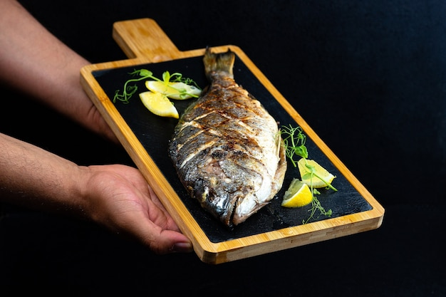 Fried fish with lemon on a dark board in male hands on a black