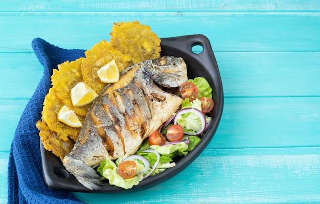 青い木製の背景の上の黒いプレートにサラダとパタコンと揚げ魚。スペースをコピーします。