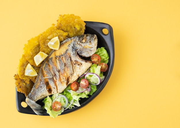 Fried fish with salad and patacones on black plate on yellow background. copy space.