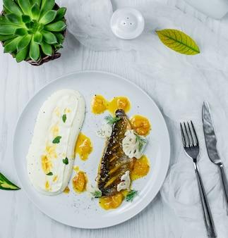 Жареная рыба с соусом в тарелке