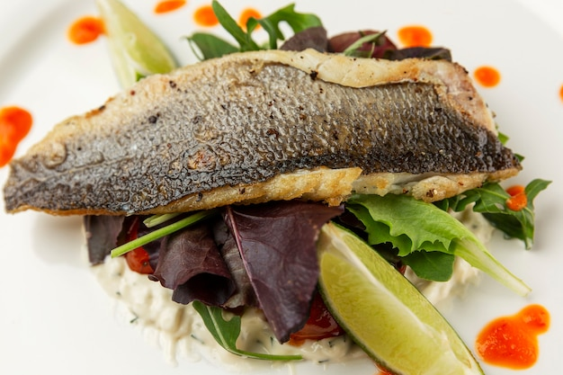 Жареная рыба с овощами. аппетитное блюдо с соусом на белой тарелке. крупный план.
