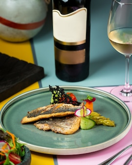Fried fish with vegetables and a bottle of white wine