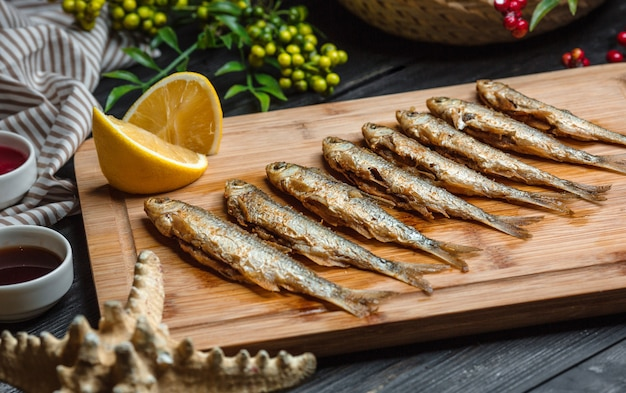 Fried fishes set on wooden board