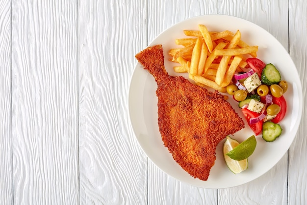 Fried flounder in breadcrumbs served with fresh vegetables, feta, olives greek salad and french fries on a white plate on a wooden table, view from above
