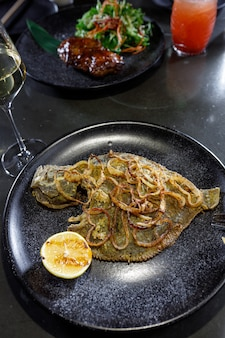 黒い粘土プレートに玉ねぎとレモンを添えて揚げたヒラメ