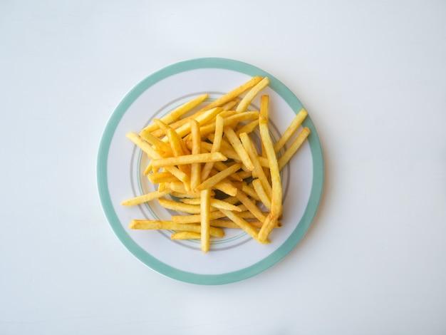 흰색 테이블에 접시에 튀긴 감자 튀김.