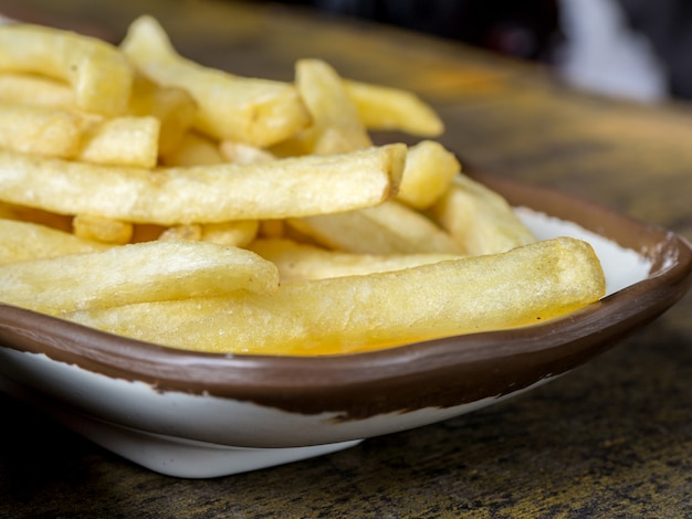 Fried french fries on a white plate with brown border on the wooden table