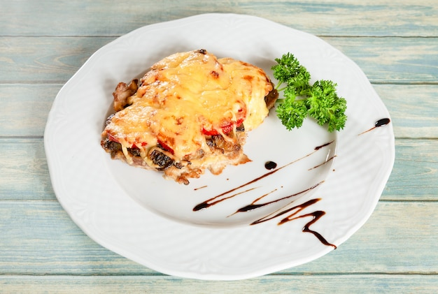 Fried french meat under cheese and vegetables
