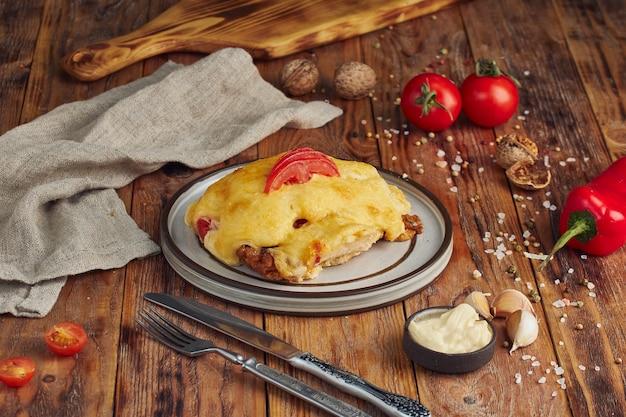 Жареное французское мясо с сыром и грибами на деревянном столе