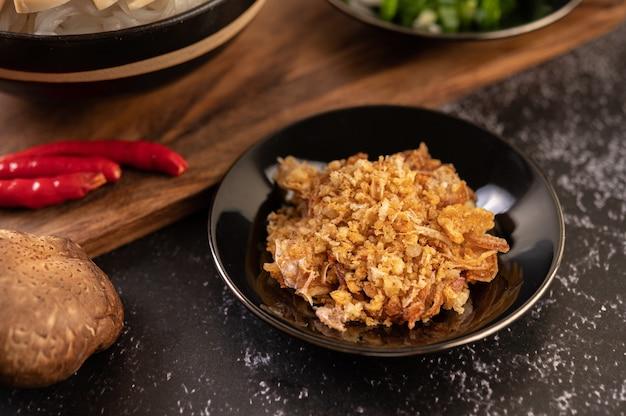 Aglio fritto sul piatto nero con peperoncino e shiitake.