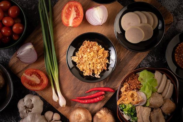 Fried garlic on black plate with chili, tomato, and shiitake.