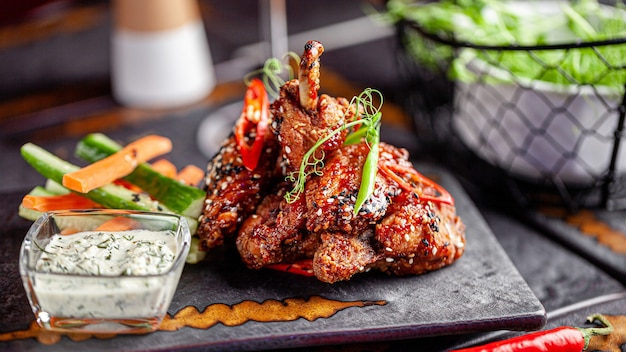 Fried glazed chicken wings and legs with white and black sesame seeds