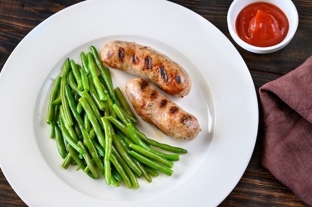 Fried green beans with grilled sausages and barbecue sauce