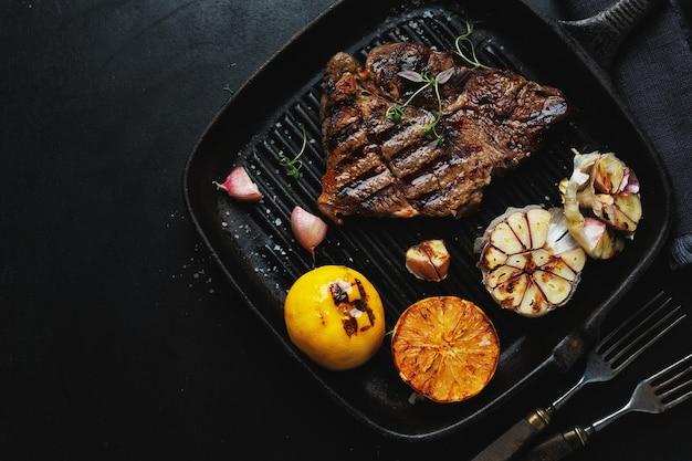 Жареный на гриле стейк из говядины с овощами на сковороде. вид сверху.