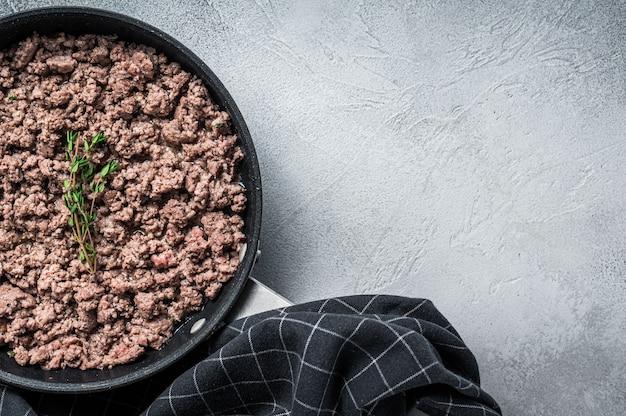 Обжарить фарш из говядины и свинины на сковороде с зеленью.