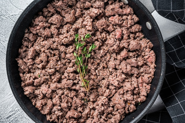 Fried ground mince beef and pork meat in a pan with herbs. white background. top view.