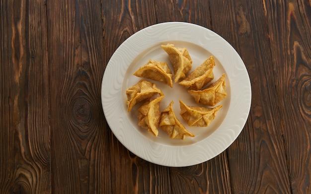 木製テーブルの皿に揚げ餃子餃子
