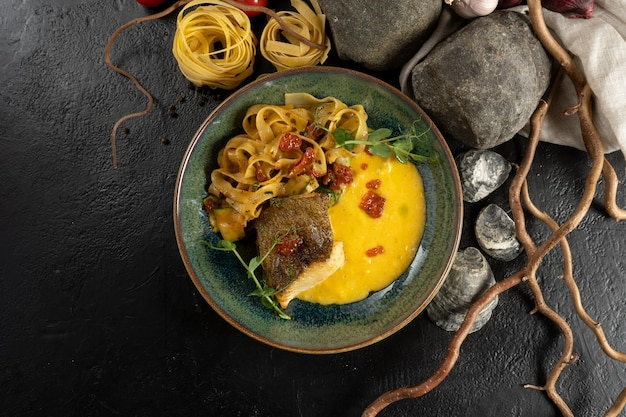 Fried halibut with tagliatelle and hollandaise sauce. hot main course of fish fillet, boiled pasta and sauce with red caviar and microgreens