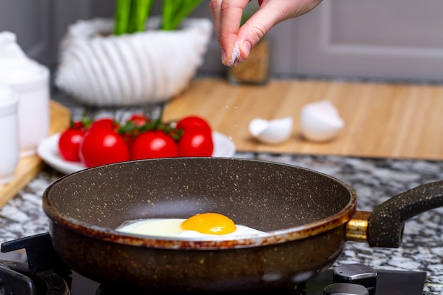 Fried homemade, chicken eggs in the frying pan sprinkling with spices for a healthy, protein breakfast