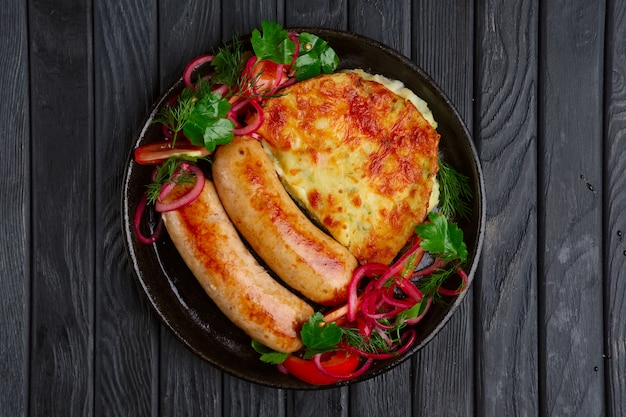 Fried homemade sausage with fried mashed potato, pickled onion and tomato