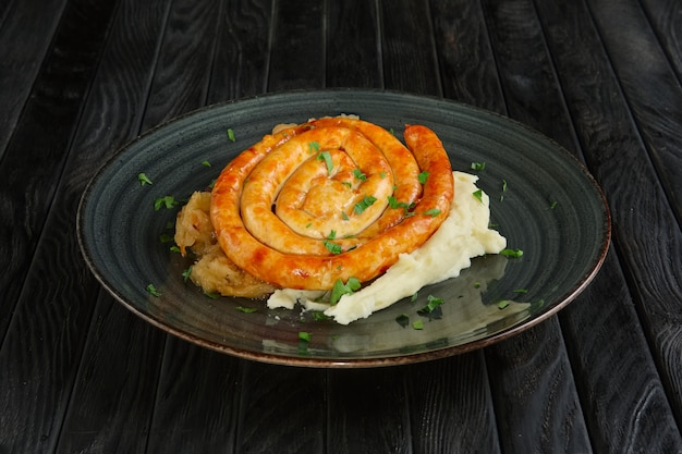 Fried homemade sausage with mashed potato and braised cabbage