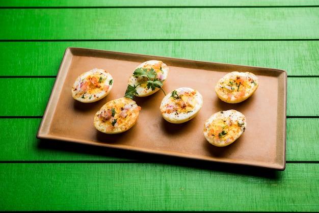 Масала из жареного горячего вареного яйца - популярный здоровый завтрак или стартовое меню из индии. с луком, кориандром, черным перцем, помидорами и солью посыпать половину яйца