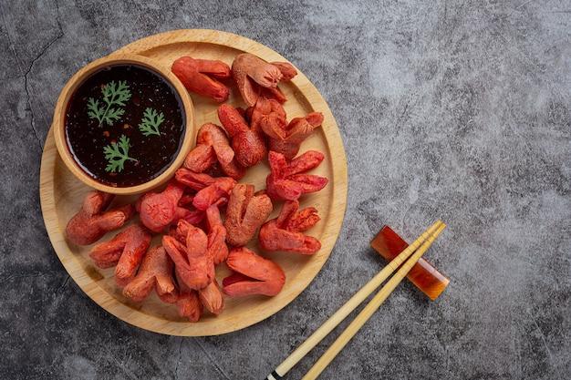 Жареный хот-дог или сосиски на темной поверхности.