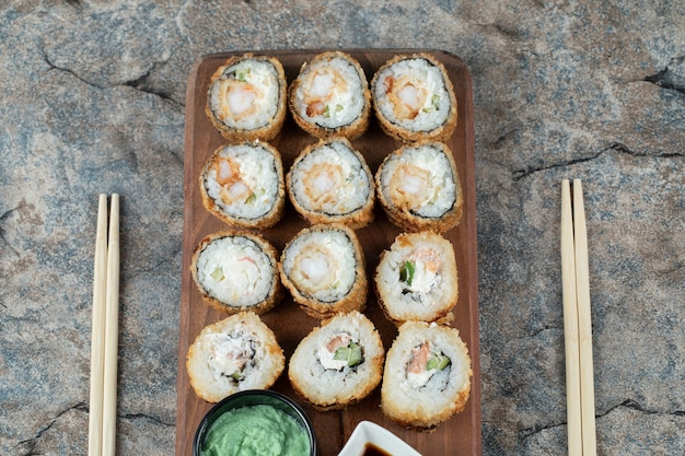Fried hot sushi rolls with cream cheese, wasabi and soy sauce on a wooden board.