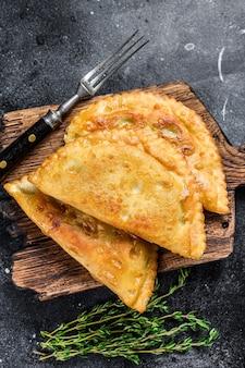 Жареные в масле чебуреки с мясом и зеленью, традиционная кавказская кухня.