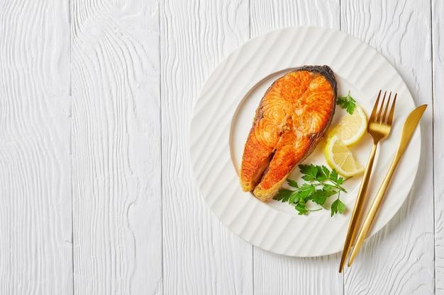 木製のテーブルの上の白いプレートにレモンスライスとパセリを添えて揚げたジューシーなサーモンステーキ、上からの水平方向のビュー、フラットレイ、空きスペース