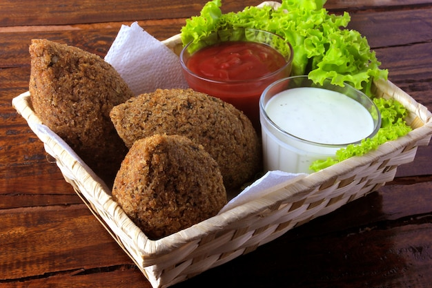Fried kibbeh with tomato sauce in a basket