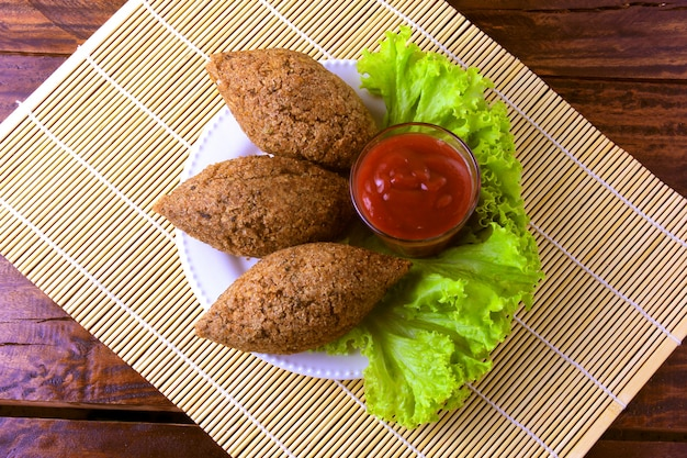 Fried kibbeh with tomato sauce on a plate