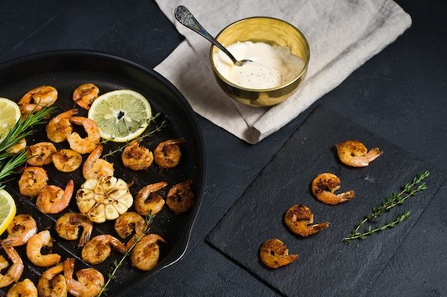 Fried king prawns in a frying pan on a black with a bowl of sauce.