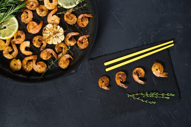 Fried king prawns in a frying pan on a black with yellow chopsticks.