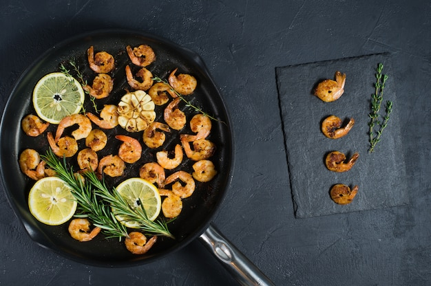 Fried king prawns in a frying pan on a black.