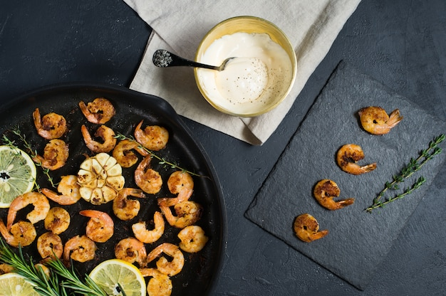 Fried king prawns in a frying pan with a bowl of sauce.