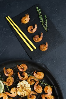 Fried king prawns in a frying pan with yellow chopsticks.