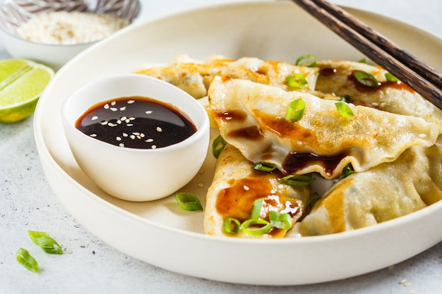 Fried korean dumplings with green onion and sauce on white plate.