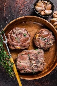 허브와 함께 나무 접시에 튀긴 양고기 목 고기 스테이크. 어두운 배경입니다. 평면도.