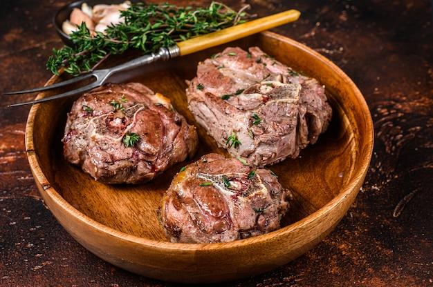 Жареные стейки из мяса шеи ягненка в деревянной тарелке с зеленью.