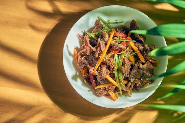 白い皿にクミンと野菜を添えた子羊の炒め物。中華料理。