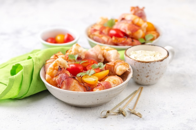 新鮮な野菜とクリーミーなソースでベーコンに包まれた殻のない揚げた大きなエビ。